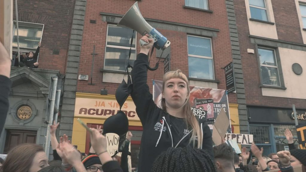 Person lifting up megaphone amongst a crowd