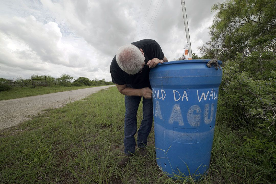 Man repairs water bucket along road in Brooks County