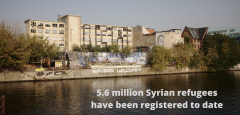 """Building along the river with the words """"5.6 million Syrian refugees have been registered to date"""" across the top."""