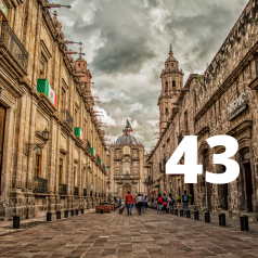 """Image of an alley of buildings with Mexican flags and the number """"43"""" on top."""